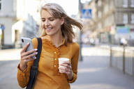 Smiling young woman with smartphone and takeaway coffee in the city - BSZF01343