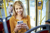 Smiling young woman using smartphone in a tram - BSZF01349