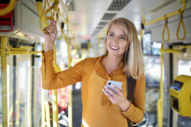 Smiling young woman with smartphone in a tram - BSZF01352
