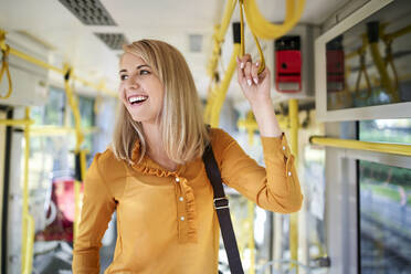 Happy young woman with smartphone in a tram - BSZF01355