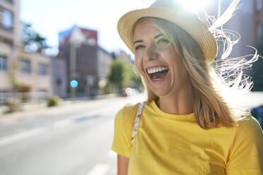 Portrait of laughing young woman in the city - BSZF01358