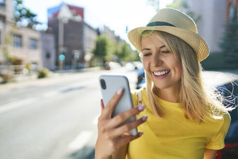Happy young woman using smartphone in the city - BSZF01361