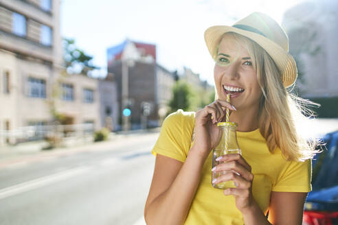 Happy young woman enjoying a drink in the city - BSZF01364
