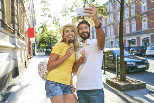 Happy young couple taking a selfie while eating ice cream in the city - BSZF01370