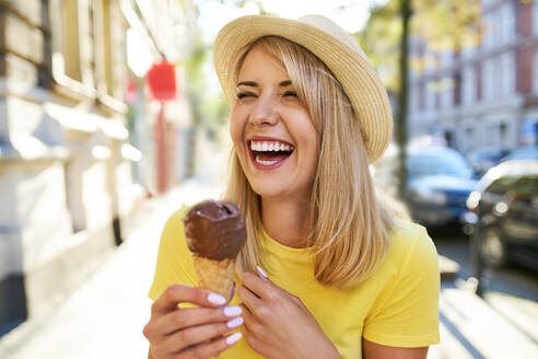 Carefree young woman enjoying an ice cream in the city - BSZF01373