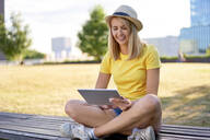 Smiling young woman sitting on a bench in the city using tablet - BSZF01376