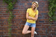 Portrait of smiling young woman standing at a brick wall - BSZF01379