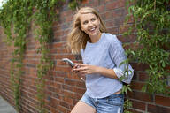 Happy young woman standing at a brick wall with smartphone - BSZF01385