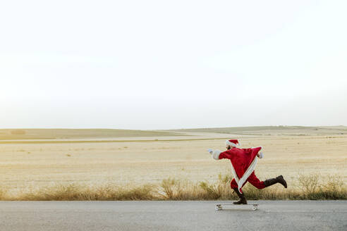 Santa Claus riding on longboard on country road - JCMF00175