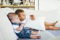 Two boys sitting on sofa and watching television at home - OCMF00619