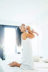 Mother playing with baby boy in the bedroom - OCMF00625