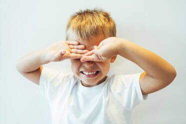 Boy covering his eyes in front of white background - OCMF00634
