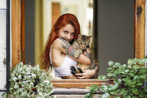 Portrait of red-haired tattooed woman with her cat at the window - JSMF01254