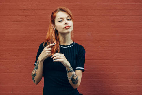 Portrait of red-haired tattooed woman standing at a brick wall - JSMF01263