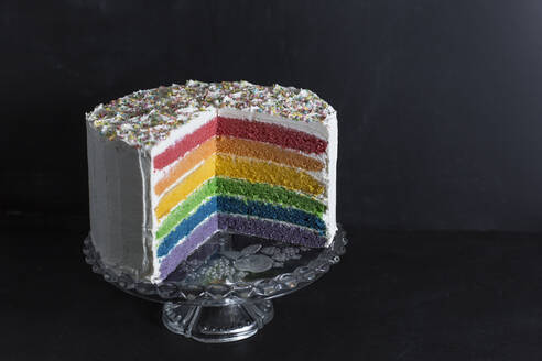 Close-up of rainbow cake against wall in studio - STBF00360