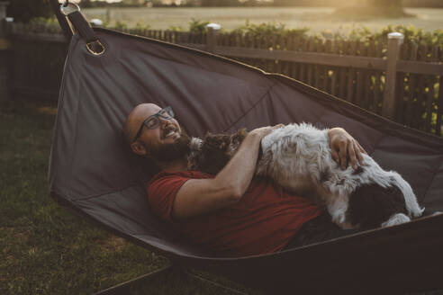Man relaxing in hammock with dog - JOHF00056