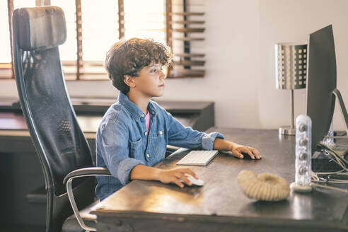 Boy sitting at desk at home using personal computer - DLTSF00063