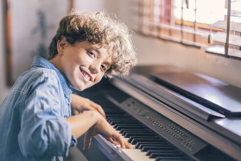 Portrait of smiling boy playing piano at home - DLTSF00066