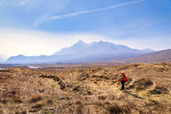 Rear view of mature woman walking on land while Cuillin mountains in background, Isle of Skye, Highlands, Scotland, UK - SMAF01502