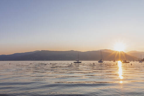 Sailboats on Lake Maggiore against clear sky during sunset, Ispra, Italy - MMAF01112