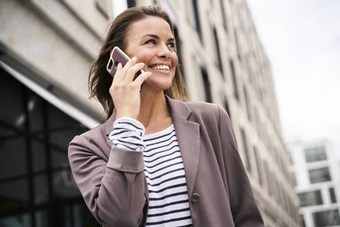 Happy businesswoman on the phone in the city - PNEF01851