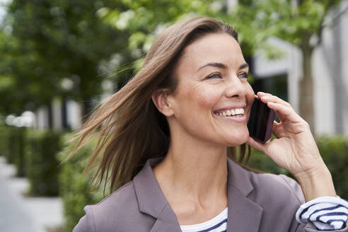 Happy businesswoman on the phone in the city - PNEF01854