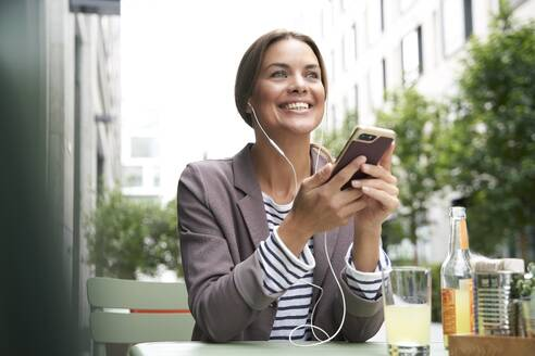 Happy businesswoman with earphones listening to music at an outdoors cafe - PNEF01860