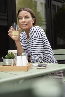 Woman having a drink at an outdoors cafe - PNEF01863