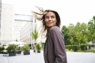 Smiling businesswoman with windswept hair in the city turning round - PNEF01866