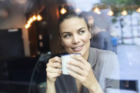Portrait of businesswoman behind windowpane in a cafe drinking coffee - PNEF01872