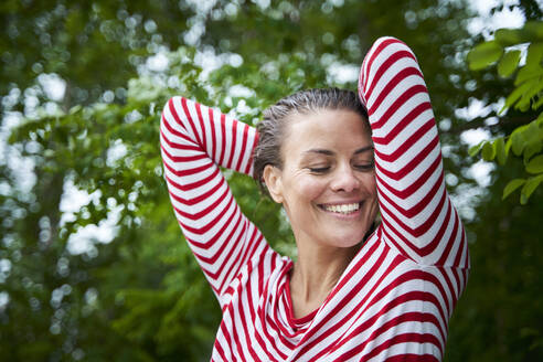 Portrait of happy woman with wet hair wearing striped top in nature - PNEF01932
