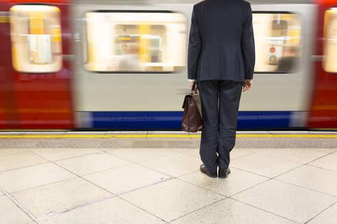 Businessman waiting for underground train at station in London, United Kingdom, England - FOLF10374
