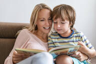 Mother and son reading a book together on couch at home - DIGF08133