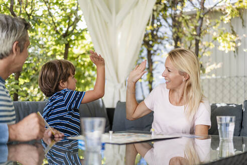 Happy mother and son high fiving after winning a game on terrace - DIGF08139