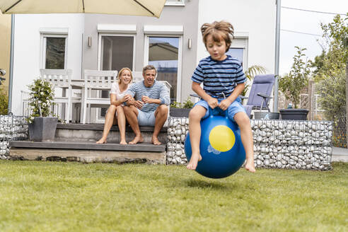 Parents watching son bouncing with hopball in garden - DIGF08145