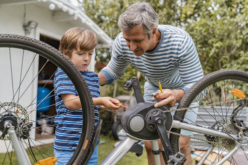 Father and son repairing a bicycle in garden - DIGF08148