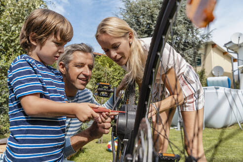 Family repairing a bicycle together in garden - DIGF08154