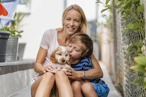 Portrait of mother snd son cuddling with cute dog puppy - DIGF08163