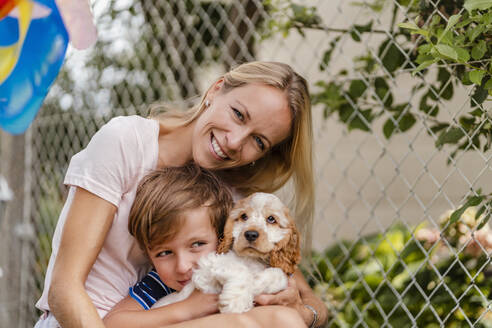 Portrait of mother snd son cuddling with cute dog puppy - DIGF08166