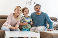 Happy parents with son playing video game on couch at home - DIGF08190