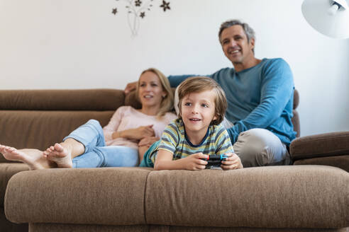 Boy lying on couch at home playing video game with parents watching - DIGF08193
