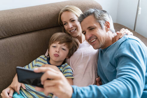 Father, mother and son taking a selfie on couch at home - DIGF08211