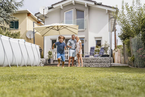 Boy running in garden with parents watching - DIGF08235