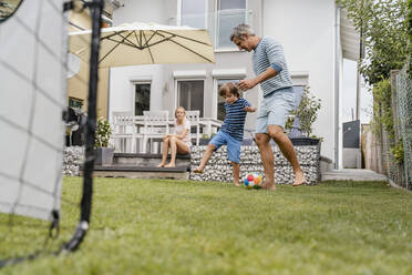 Father and son playing football in garden - DIGF08238