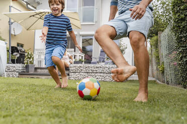 Father and son playing football in garden - DIGF08241