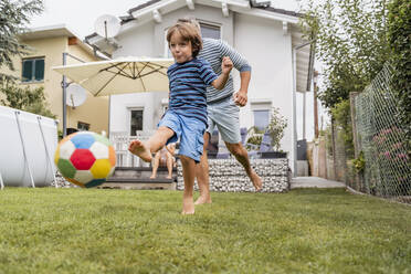 Father and son playing football in garden - DIGF08244