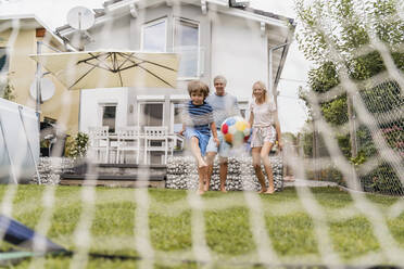 Happy family playing football in garden - DIGF08247