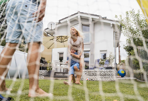 Happy family playing football in garden - DIGF08250