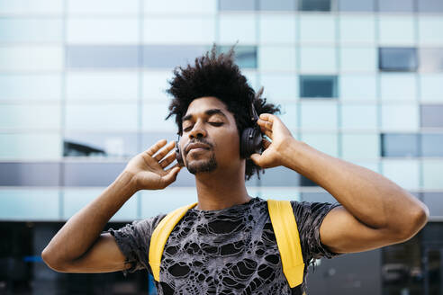 Portrait of man listening music with cordless headphones, Barcelona, Spain - JRFF03703