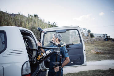 Mature man stowing bike into his off-road vehicle - OCMF00641